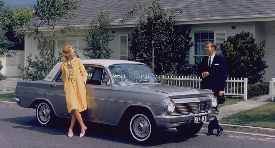 A Couple Standing by a Classic Holden