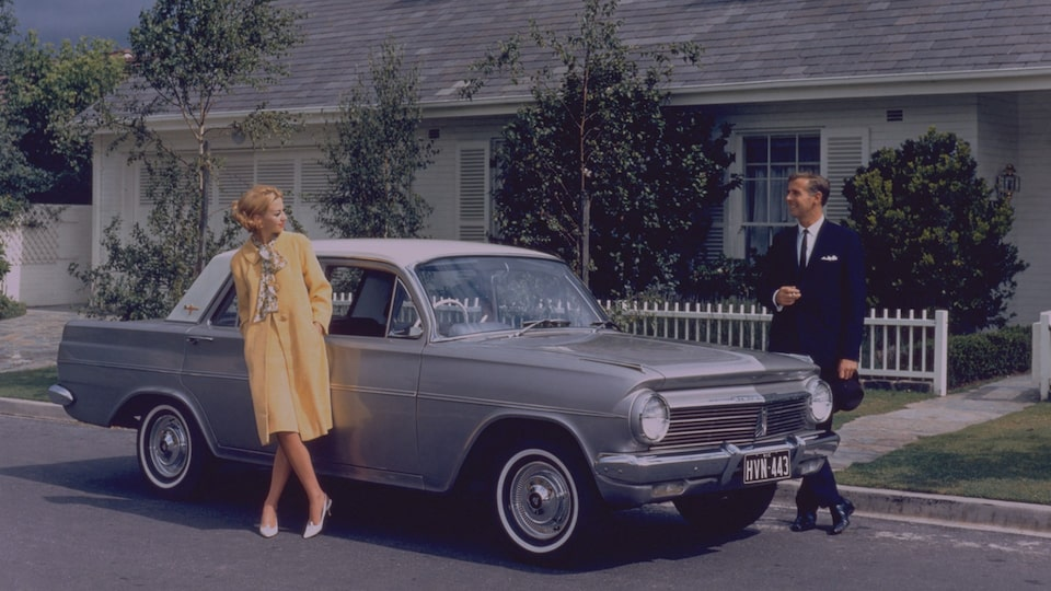 A Man and Woman Standing by a 1950s Holden